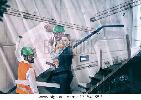 Crane and building construction site against happy businesswoman and architects standing on a staircase discussing with blueprint