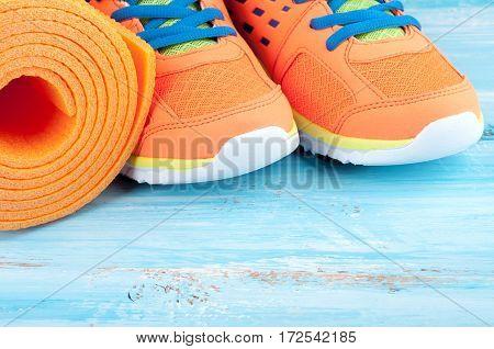 Yoga mat and sport shoes on blue wooden background. Concept healthy lifestyle and sport. Sport equipment. Selective focus