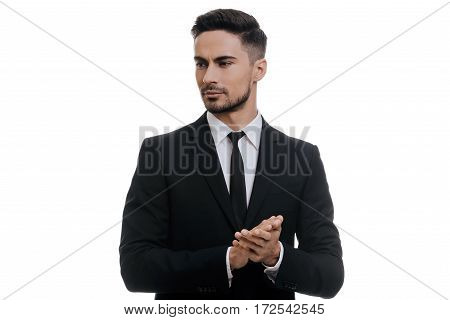 Confidence and charisma. Handsome young man in full suit holding hands clasped and looking away while standing against white background