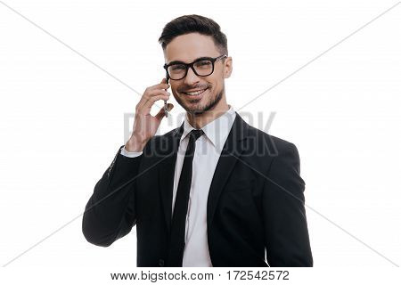 Good business talk. Handsome young man in full suit talking on smart phone and looking at camera while standing against white background
