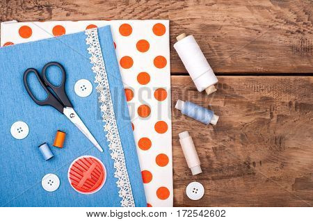 Handmade and sewing background. Fabric for sewing lace and accessories for needlework on old wooden background. Spool of thread scissors buttons sewing supplies. Set for needlework top view