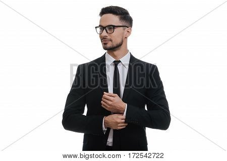Used to look perfect. Handsome young man in full suit adjusting his sleeve and looking away while standing against white background