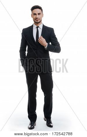 Portrait of elegance. Full length of handsome young man in full suit adjusting his jacket and holding one hand in pocket while standing against white background