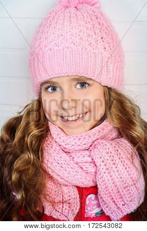 Winter clothes concept. Pretty smiling girl with long curly hair wearing pink knitted hat and scarf and smiling at camera.
