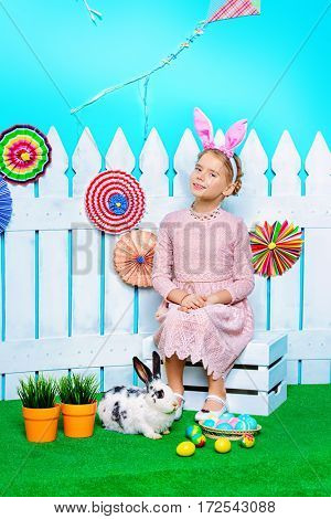 Cute happy little girl sitting with Easter Bunny in spring decorations. Easter Bunny and painted eggs. Kid's fashion.