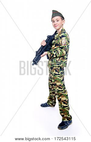 Different professions. A boy  dressed in military costume holding a gun. Soldier. Isolated over white.