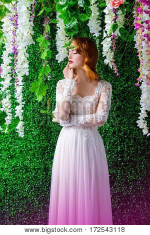 Portrait of a charming young woman in the flowered garden. Spring Fantasy. Beautiful bride girl portrait. Fashion shot.