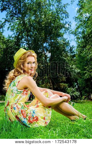 Happy romantic girl sitting on a green lawn in the park on a sunny summer day. Smiling young woman outdoor. Holiday, vacation.