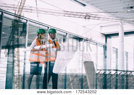 Crane and building construction site against architects discussing with blueprint