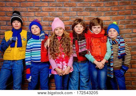 Group of happy joyful children posing together at studio by the brick wall. Kid's fashion. Winter clothes.