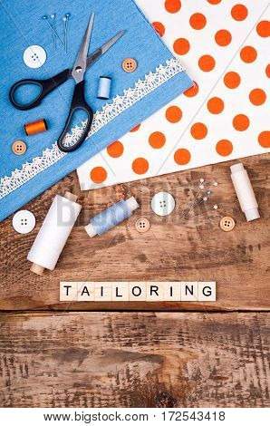 Tailoring background. Fabric for sewing lace and accessories for needlework on old wooden table. Spool of thread scissors buttons sewing supplies. Set for needlework top view