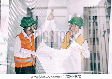 View of modern office building against architects holding blueprint while giving high five