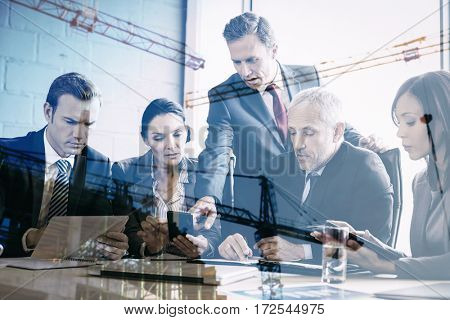 Crane and building construction site against business people having meeting in conference room