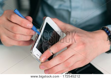 Separating smartphone screen in repair shop. Closeup of repairman hands holding broken mobile phone and separating it. Electronic fixing, modern technology, business concept