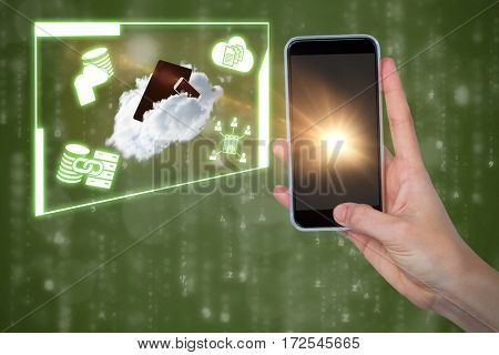 Human hand holding mobile phone against green background