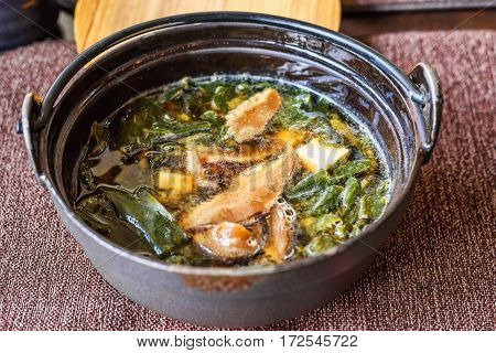 Traditional japanese miso soup in a black bowl, with tofu cheese, mushrooms and seaweed, restaurant table, close up