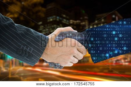 Business people shaking hands against illuminated roads by building in city