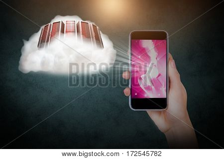 Hand holding mobile phone against black background