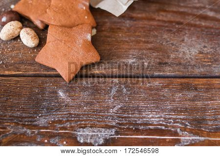 Sweet gingerbread stars on wooden background flat lay. Top view on rustic table with chocolate cookies, free space for advertisement. Menu, dessert, confectionery concept