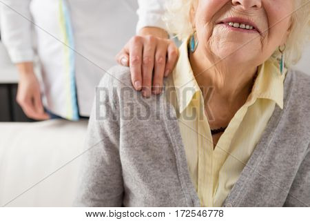 Nurse holding her hand on seniors shoulder