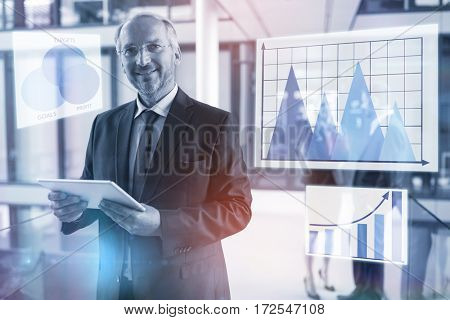 Graph against portrait of businessman holding digital tablet and colleagues talking in background