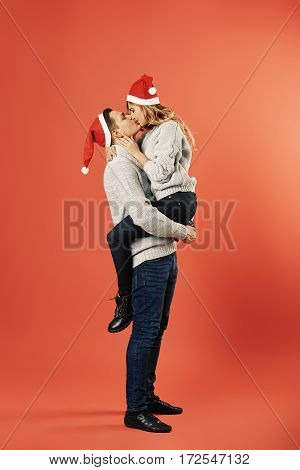 Cheerful couple in winter clothes hugging and kissing