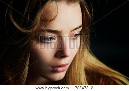 Beautiful girl looking to the side, in profile, Hair flying. Drama. Studio photography in low key on a background