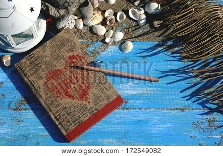 Blue wooden background with sand and shells antique notebook with red heart .