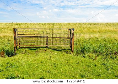 Rusty iron gate in front of a dike in the Netherlands. It is a sunny day in the summer seaon.