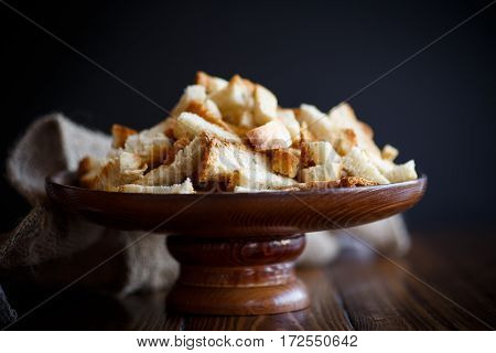 fried croutons of homemade bread on black background