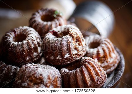 sweet honey muffins in powdered sugar on a wooden table