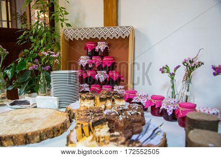Jars of jam are on the buffet table in the shape of a pyramid