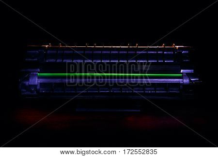 Laser toner cartridge on a dark background with blue and yellow lighting.