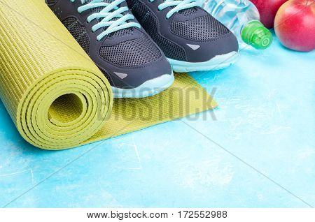 Yoga mat sport shoes apples bottle of water on blue background. Concept healthy lifestyle healthy food sport and diet. Sport equipment. Copy space