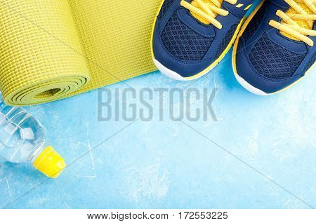 Yoga mat sport shoes and bottle of water on light background. Concept healthy lifestyle sport and diet. Sport equipment. Copy space