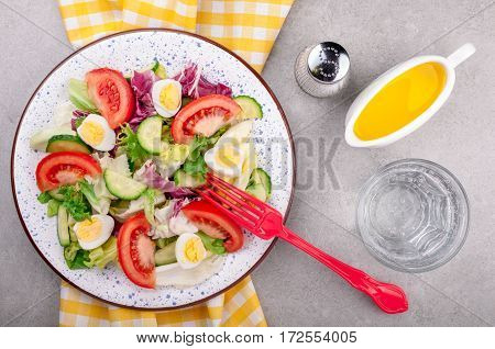 Lunch with salad and mineral water. Healthy food and diet concept. Fresh salad with vegetables tomatoes cucumbers mix salad leaves eggs and olive oil on grey background top view. Vegetarian food