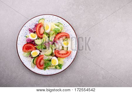 Fresh salad with vegetables tomatoes cucumbers lettuce salad leaves and eggs on grey background top view and copy space. Healthy food and diet concept. Vegetarian food