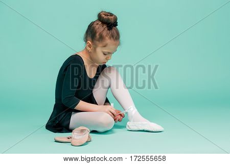 Beautiful little ballerina in black dress for dancing sitting on the floor and puting on foot pointe shoes on blue studio background