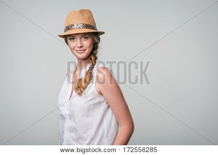 Beautiful smiling woman wearing summer straw fedora hat in carefree stance