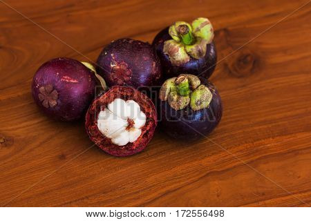 Fresh juicy mangosteens on wooden brown table and wooden background. Close-up