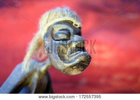 Scary-looking carved wooden sculpture with red background. Focus on chin.