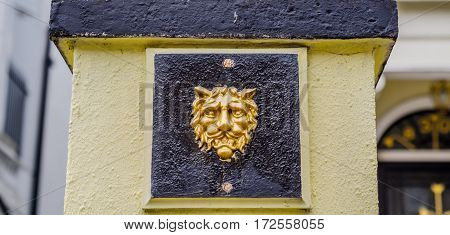 interesting decoration in the shape of a lion's head placed on the front of the pedestal at the entrance gate on estates architectural decoration gold