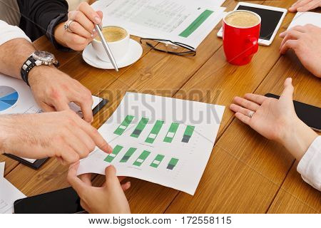 Business meeting. Hands closeup at modern office workplace, wooden desk. Team discussion, data analysing, show information on papers with diagram. Brainstorming with partners