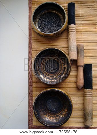three Tibetan bowls with sticks on the background of straw Mat