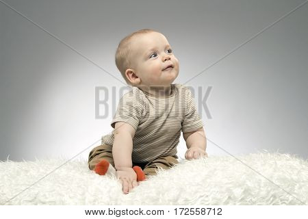 Enigmatic baby is looking away on the grey background. Studio shot