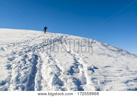 Skier Walks Up To The Top.