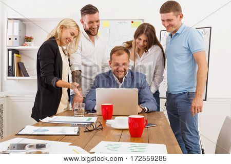 Happy business people laugh near laptop in the office. Successful corporate team of female and male coworkers joke and have fun together at work, look at internet site