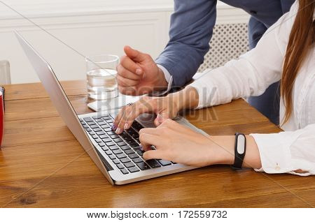 Closeup of businessman's hand supervising his assistant's work on the laptop computer. Man helps woman in the office, unrecognizable people. Boss checking secretary's job execution