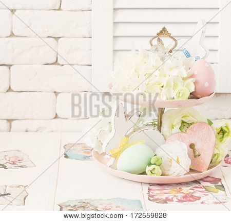 Easter pastel colored decoration in shabby chic style on tier plate.