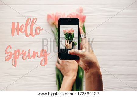 Hello Spring Text Sign, Hand Holding Phone Taking Photo Of Stylish Flower Flat Lay, Pink Tulips On W